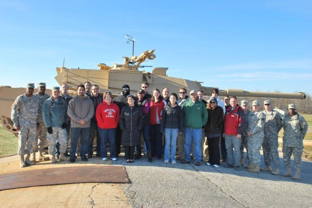 Greening course participants pictured standing in front of the tank/track vehicle after it climbs a 45 to 60 degree slope at the Aberdeen Test Center.