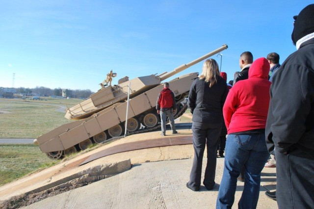 Greening course participants pictured standing in front of the tank/tracked vehicle after it climbs a 45 to 60 degree slope at the Aberdeen Test Center.