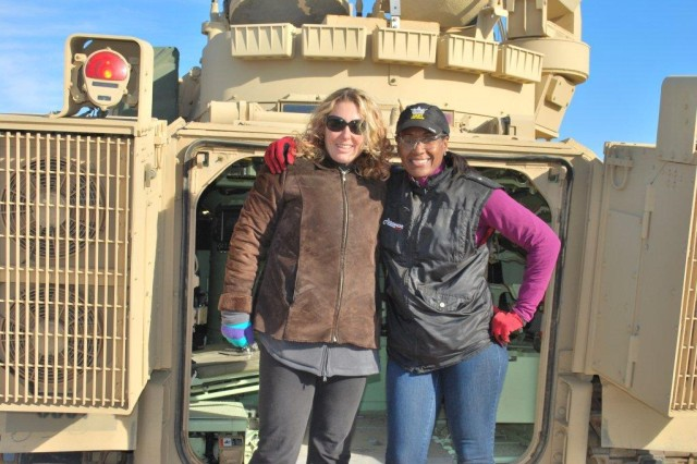 Samantha Napier, HRED, Orlando, Fla., and Laura Bell, Signal Network Enterprise Center, pose for a photo after riding in one of the Aberdeen Test Center vehicles.