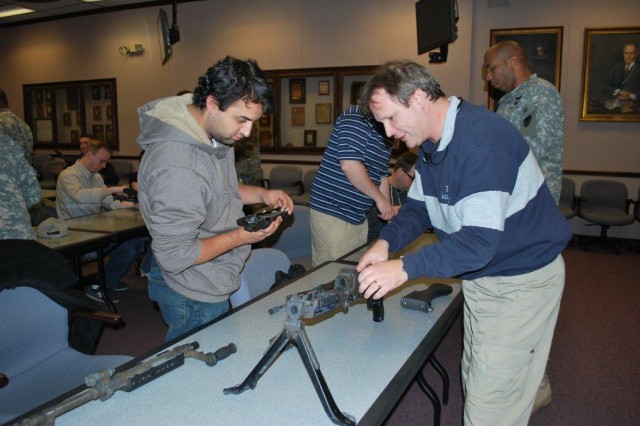 Neeraj Shukla, SLAD, and Alan Kalb, LABOPS, work together to assemble one of the rifles during the course instruction.