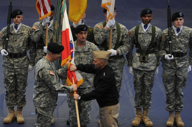 Adm. James Stavridis, commander of the U.S. European Command (in black jacket), passes the U.S. Army Europe flag to Lt. Gen. Donald M. Campbell Jr. during Campbell's assumption of command ceremony at Clay Kaserne in Wiesbaden, Germany, Jan. 9 2013.