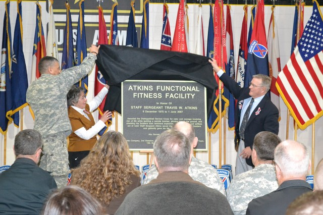 Maj. Gen. Stephen J. Townsend, Fort Drum and 10th Mountain Division (LI) commander, joins Jack and Elaine Atkins in unveiling a plaque dedicating the Mountain Functional Fitness Facility in memory of their son, Staff Sgt. Travis W. Atkins, who sacrificed his life to save his fellow Soldiers while serving in Iraq in 2007.