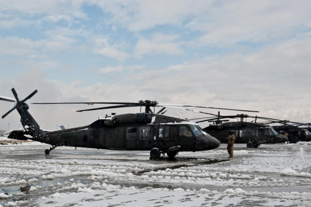 Snow flies off the rotor blades of a UH-60 Black Hawk helicopter as its rotors spin up to speed during a maintenance run up at the 101st Combat Aviation Brigade flight line, Bagram Air Field, Afghanistan, Jan. 12, 2013. (U.S. Army photo by Sgt. Duncan Brennan, 101st CAB public affairs)