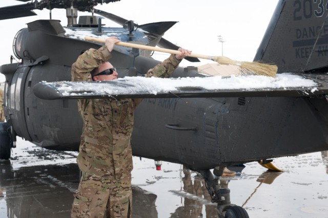 Spc. John Lutjen, A Company, 6th Battalion, 101st Combat Aviation Brigade, clears snow off the stabilator of a UH-60 Black Hawk helicopter at Bagram Air Field, Afghanistan, Jan. 12, 2013. (U.S. Army photo by Sgt. Duncan Brennan, 101st CAB public affairs)