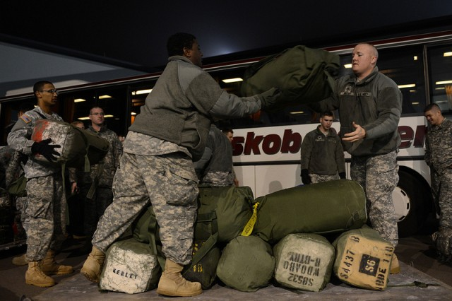 Army Spc. Gregory Brinson and Staff Sgt. Paul Emory, 10th Army Air and Missile Defense Command, stack deployment bags on a pallet on Ramstein Air Base, Germany, Jan. 9. The 10th AAMDC forces will support the NATO led coalition that will augment Turkey's air defense capabilities and contribute to the de-escalation of the crisis along the border.