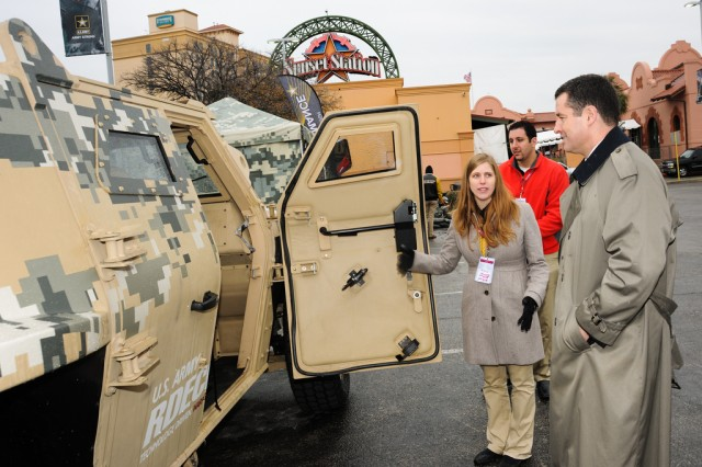 TARDEC engineer Rachel Agusti (left) shows Research, Development and Engineering Command Director Dale Ormond the Fuel Efficient Demonstrator Alpha concept vehicle, at the Army Strong Zone outside the Alamodome in San Antonio, which is where the 2013 U.S. Army All-American Bowl was played, Jan. 5, 2013.