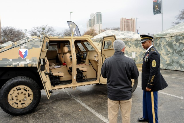Research, Development and Engineering Command Command Sgt. Maj. Lebert Beharie (right) discusses the Fuel Efficient Demonstrator Alpha concept vehicle at the Army Strong Zone, outside the Alamodome in San Antonio, which is where the 2013 U.S. Army All-American Bowl was played, Jan. 5, 2013.
