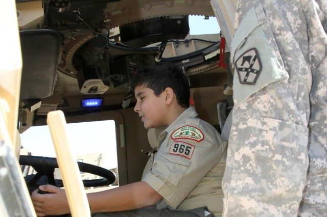 Pfc. De'Marcus Salter, a 47th Transportation Company motor transport operator, explains features of a mine-resistant, ambush-protected vehicle to international Boy Scout Yousef Abdel-Rahman, 12, Direct Service Troop 965, at Camp Arifjan, Kuwait, Jan. 12, 2013. Salter, from Monoroeville, Ala., helped give the Scouts a tour of the vehicles and explained their features.