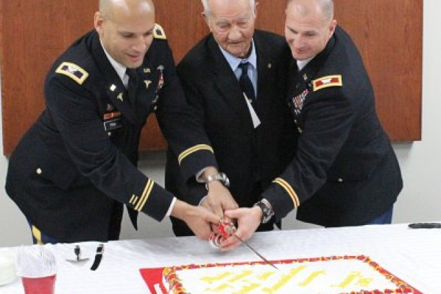 "Col. Joseph S. Pina, Kenner Army Health Clinic commander, Howard Mosier and Col. Edward M. Daly, Chief of Ordnance and commandant of the U.S. Army Ordnance School cut a cake at a reception following the dedication of Mosier Troop Medical and Dental Clinic. Howard Mosier is the brother of Corp. William Clarence ""Billy"" Mosier, a decorated Korean War hero whom the clinic is named after."