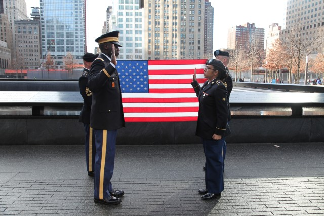 Chief Warrant Officer 2 Magnus Thorpe, property book officer, 704th MI Brigade, administers the oath of reenlistment to Spc. Bettina Moore, supply clerk, 704th MI Brigade at the 9/11 Memorial in New York, Jan. 10.