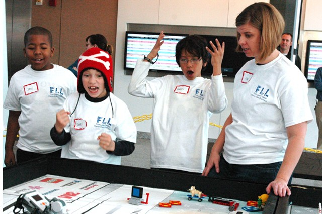 (From left) Manor View Brainiacs team members Jerel Mitchell, Daniel Hankinson, Gabriel Ramirez, and coach Lisa Evans watch as their autonomous robot performs a task during the FIRST LEGO League Challenge qualifying rounds  at the U.S. Army Test and Evaluation Command headquarters Jan. 5.