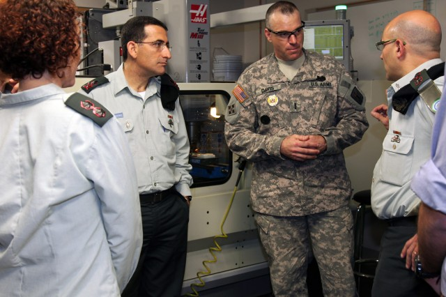 Col. Ziv Avtalion, Israeli Defense Force Organization and Planning Department head (right), asks Chief Warrant Officer 4 Mark G. Davis, Allied Trades instructor, questions regarding the computer-aided design milling machines used in the U.S. Army Ordnance School's Allied Trades course, Jan. 14, 2013, at Fort Lee, Va.