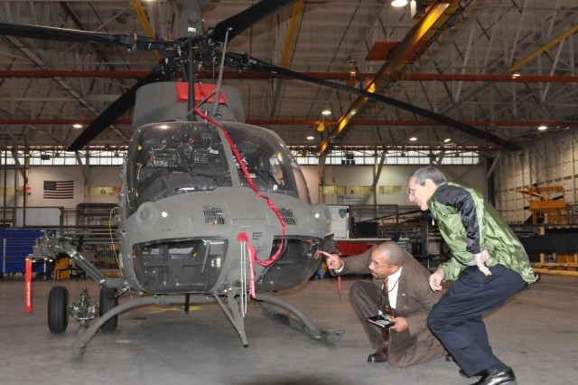 Roy Hollins, director of aircraft production, identifies some of the distinguishing feature on a OH-58 D Kiowa Warriors to the Alan Estevez, assistant secretary of Defense for Logistics & Materiel Readiness.