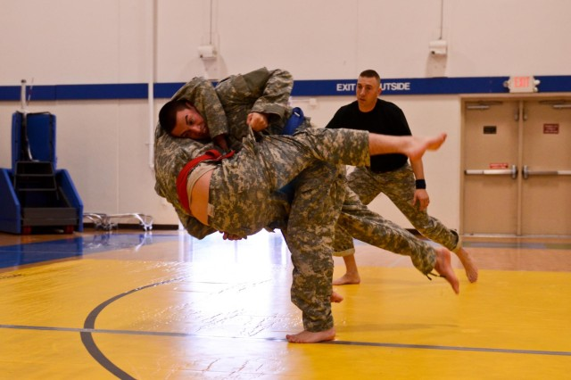 Pfc. William Gusman, a signal support systems specialist with 1st Battalion (155 mm Towed), 377th Field Artillery Regiment, 17th Fires Brigade, takes Sgt. David Evans, a platoon sergeant with 256th Signal Company, 1-377 FA, to the ground during a combatives tournament at McChord Fitness Center Dec. 14. (U.S. Army photo by Spc. Nathan Goodall, 17th Fires Brigade Public Affairs)