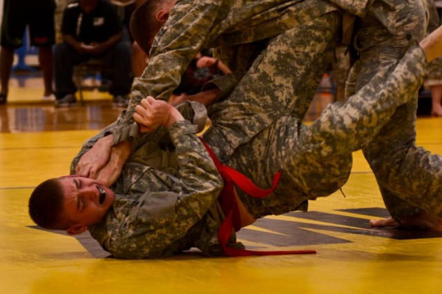 Pfc. Justin Stuart, 256th Signal Company, 308th Brigade Support Battalion, 17th Fires Brigade, fights above Spc. Justin Owens, a multiple launch rocket system crew member with Battery A, 5th Battalion (HIMARS), 3rd Field Artillery Regiment, 17th Fires Brigade, during a combatives tournament at McChord Fitness Center Dec. 14. (U.S. Army photo by Spc. Nathan Goodall, 17th Fires Brigade Public Affairs)
