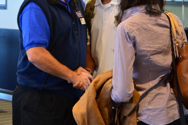 Spc. Chris Anderson and his wife, Spc. Jasmine Anderson, both of the 2nd Stryker Brigade Combat Team, 2nd Infantry Division, are greeted by a USO representative, Jan. 11, 2013, after arriving at the Seattle-Tacoma International Airport from the Walter Reed National Military Medical Center in Bethesda, Md. Anderson, who returned to surprise his comrades who returned from Afghanistan last week, lost his left after stepping on an improvised explosive device during a dismounted patrol. He has not seen the men in his company since the day of the blast.