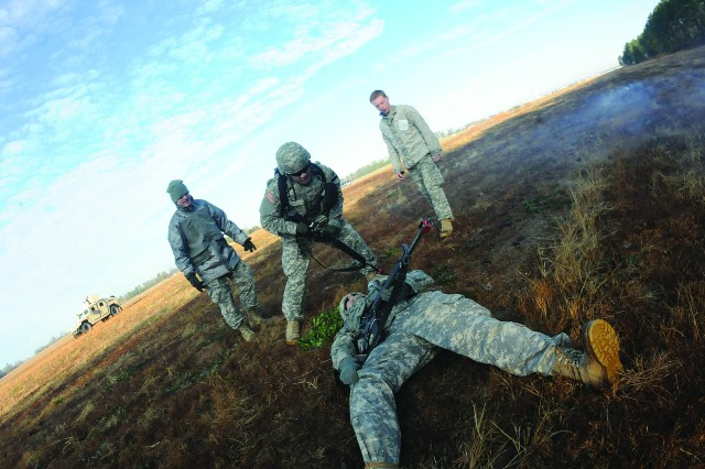 Second Lt. Michael Karaty comes to the aid of an unidentified buddy who was wounded by gunfire after a village disturbance during the BOLD FTX pilot training exercise Jan. 9