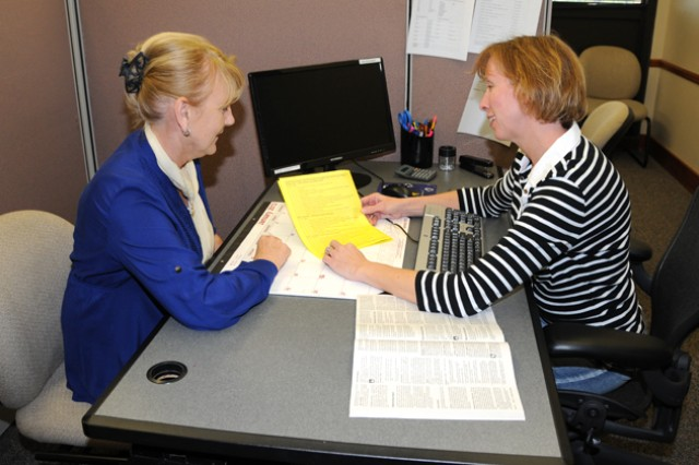 Gaile Avelyn and Erin McGlone, tax preparers at the Tax Assistance Center, go over tax forms at the tax center offices in Bldg. 5700 Jan. 11 in preparation for the upcoming tax season. The tax center will open its phone lines Jan. 22 to begin making appointments for its Jan. 24 opening.