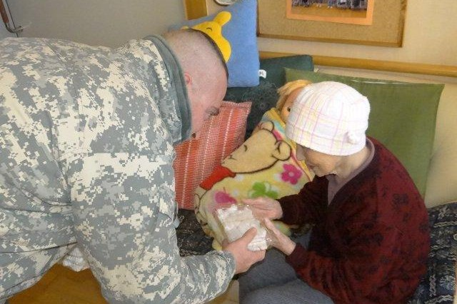 1st Sgt. Daniel Perdue, detachment 10 first sergeant, 100th Missile Defense Brigade, presents a mochi to a resident of a nursing home in Tsugaru, Japan, Dec 28. The mochi, a rice cake made from pounding cooked rice, was made by members of the detachment and members of the Japanese Air Self-Defense Force during a traditional ceremony.