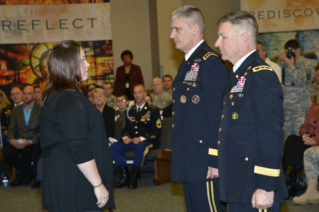 Gen. David Rodriguez, the commander of U.S. Army Forces Command, and Maj. Gen. James C. McConville, 101st Airborne Division and Fort Campbell commanding general, present the Distinguish Service Cross to the widow and mother of Staff Sgt. Eric Shaw. Shaw was posthumously awarded the second highest military award for valor that can be given to a service member, based on Shaw's actions while serving as a squad leader with 1st Brigade, 101st Airborne Division, in Kunar Province, Afghanistan, in June 2010.