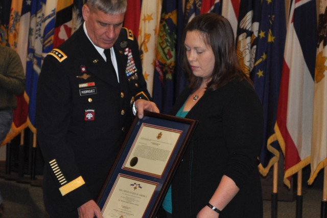 Audrey R. Shaw, widow of Staff Sgt. Eric Shaw, accepts the Distinguished Service Cross in honor of her husband's actions in Afghanistan