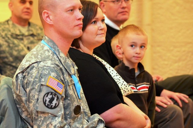 Sgt. 1st Class Matthew Favory, Army Sustainment Command's first Sergeant Audie Murphy Club inductee, sits with his wife, Amanda, son, Karsen, 5, and father, Charles Favory, during the ceremony. In between Karsen and Mr. Favory is younger brother, Lucas, 4. (Photo by Jasmine Phillips, ASC Public Affairs)