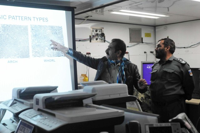 Two of the Afghan officials ask questions regarding finger print patterns at the Afghanistan Captured Material Exploitation lab at Kandahar Airfield, Jan 16, 2013.( U.S. Army photo by Sgt. Ashley Bell)