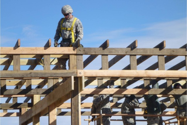 Soldiers from the 377th Engineer Company install rafters on a pole barn.