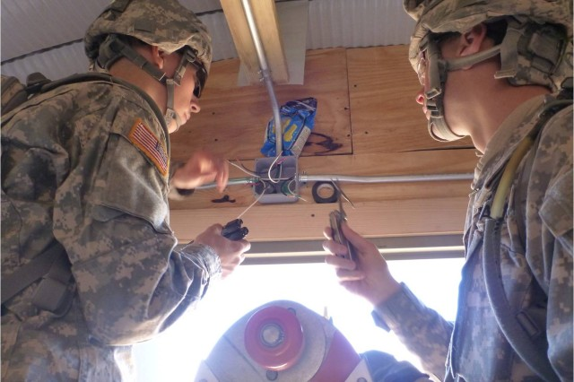 Soldiers from the 377th Engineer Company install an electrical switch in a pole barn.