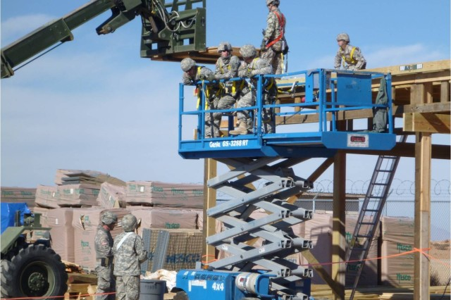 Soldiers from the 377th Engineer Company load plywood onto the roof of a pole barn.