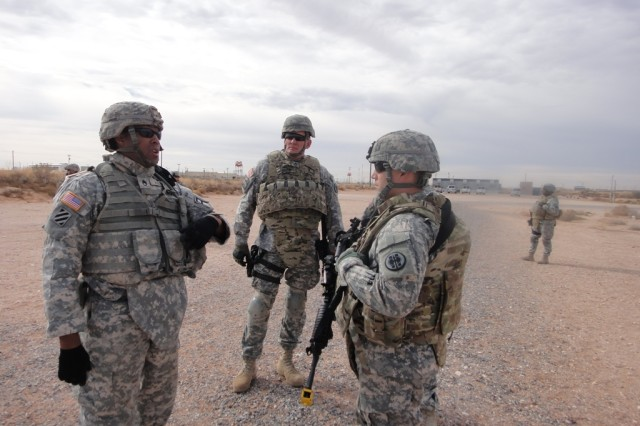 Staff Sgt. Vincent Adams, left, an observer controller/trainer with 1st Battalion, 361st Engineer Battalion, 5th Armored Brigade, mentors 352nd Military Police Company and 382nd Military Police Detachment Soldiers on a C-IED lane.