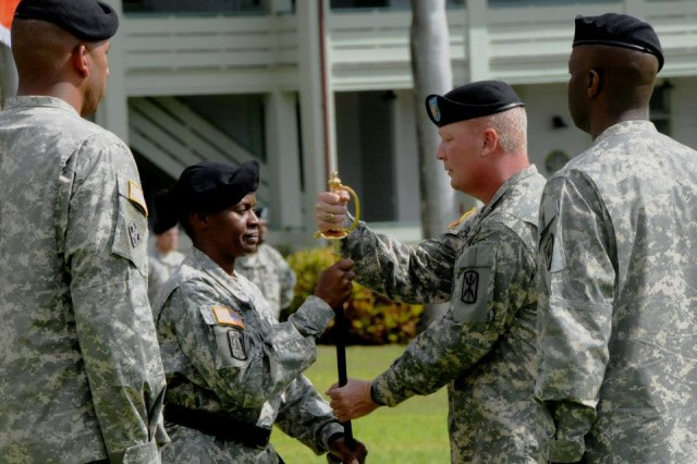 "FORT SHAFTER, Hawaii "" Command Sgt. Maj. Travis Cherry, 516th Signal Brigade outgoing Command Sgt. Maj., accepts the unsheathed Noncommissioned Officer's sword from Sgt. Maj. Tara Bryan, Headquarters and Headquarters Company Sgt. Maj., as he prepares to relinquish responsibility for the brigade Soldiers.  311th Signal Command (Theater) Command Sgt. Maj. Kevin Thompson (right), and incoming Brigade Command Sgt. Maj., Command Sgt. Maj. Allen Braswell, watch as they await their turn to pass the sword in the brigade change of responsibility ceremony, at historic Palm Circle, here, Jan 17.  (Photo by Lin Clark Miller, 516th Signal Brigade Unit Public Affairs Representative)"