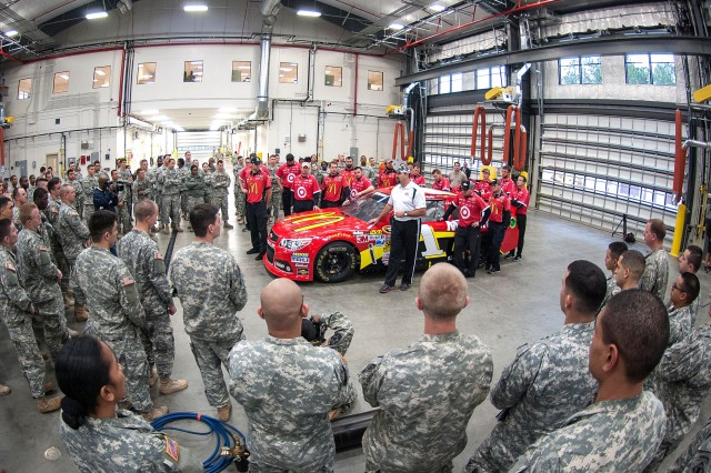 Brett Cumming, pit crew coach for the Earnhardt Ganassi McDonalds 1 Car, speaks to Fort Bragg soldiers about the teamwork required to be a member of a NASCAR pit crew.  Cumming and his team visited Fort Bragg, N.C., Jan. 17, 2013, and hosted the NASCAR Pit Crew Challenge, an event that put soldiers in the roles of a NASCAR pit crew.  (U.S. Army photo by Capt. Thomas Cieslak)