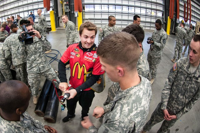 """Jeremy Fuller, a tire changer for the Earnhardt Ganassi McDonald's 1 Car, demonstrates to Spc. Jacob Arent how to properly hold an air gun while removing a tire from a racing car during the NASCAR Pit Crew Challenge held Jan. 17, 2013, on Fort Bragg, N.C.  Arent and his team of paratroopers from the 2nd Battalion, 504th Parachute Infantry Regiment, won the challenge by changing four tires in 28.93 seconds """" the fastest of nine teams participating in the event.  (U.S. Army photo by Capt. Thomas Cieslak)"""