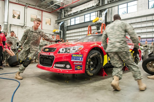 """Spc. Jacob Arent follows his pit crew team leader, Sgt. 1st Class William Pittman, around the Earnhardt Ganassi McDonald's 1 car during the NASCAR Pit Crew Challenge held Jan. 17, 2013, on Fort Bragg, N.C.  The team of paratroopers from the 82nd Airborne Division's 2nd Battalion, 504th Parachute Infantry Regiment, won the challenge by replacing four tires in 28.93 seconds """" the fastest of nine teams participating in the event.  (U.S. Army photo by Capt. Thomas Cieslak)"""