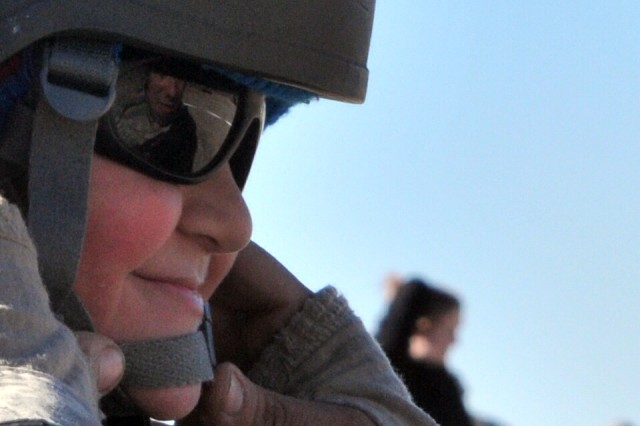 Family member Nicky Hernandez gets his chin strap adjusted on his advanced crew helmet during the 1st Battalion, 17th Field Artillery's family day event Jan. 17 on Forward Operating Base Mow-Way. Nicky's father, Spc. Brian Hernandez, artilleryman, is reflected off the lens. The event was dubbed '1-17th Day on Jan. 17 at 1:17 a.m.'