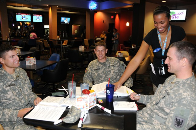 Phylicia Thomas, waitress at The Landing Zone, serves 2nd Lt. Michael Karolchik, 2nd Lt. Thomas Chandler and W01 Christopher Scott, B. Co., 1st Bn., 145th Avn. Regt., at lunchtime.