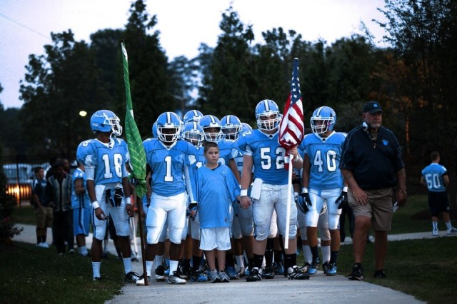 Kyle Dowgin (center), 10, leads the Notre Dame High School football team out before a game in Lawrenceville, N.J. The American flag was presented to Coach John McKenna (far right), and was flown in Southern Afghanistan over the 117th Combat Sustainment Support Battalion's compound on Kandahar Airfield. Kyle is the son of Maj. Edward Dowgin, the 117th's executive officer.
