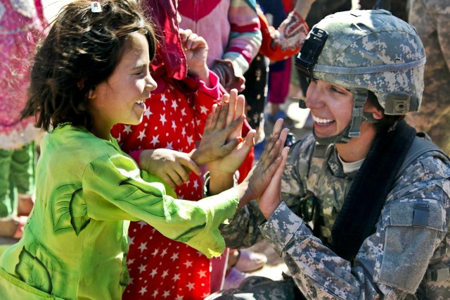 Women today are serving in harm's way and have been for the last decade. Now the Army will be expanding the opportunities for women to serve in more combat-related military occupational specialties. Here, Sgt. Stephanie Tremmel, with the 86th Special Troops Battalion, 86th Infantry Brigade Combat Team, interacts with an Afghan child while visiting the village of Durani.