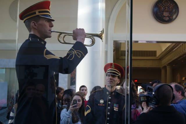 The U.S. Army Band's bugler, Staff Sgt. Jesse Tubb, looks at a life-sized statue of himself playing Taps in Arlington National Cemetery's (Va.) remodeled welcome center during a ribbon-cutting ceremony for the facility, Jan. 20, 2013.