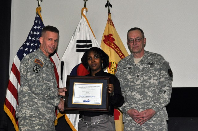 Claudette Mohn, CYSS services coordinator for USAG Yongsan's Directorate of Family and Morale, Welfare and Recreation, center, receives the NAEYC Accreditation certificate presented by Col. Michael E. Masley, left, and Command Sgt. Maj. Daniel L. Willing, Jan. 14. (U.S. Army photo by Pfc. Jung Jihoon)