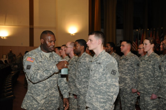"WIESBADEN, Germany (January 17, 2013) ""  Command Sgt. Maj. Gerald L. Tyce, 5th Signal Command, ""wets"" newly inducted NCOs rank symbolizing welcoming them into the NCO corps.  More than 100 Soldiers from nine units based on Lucius D. Clay Kaserne passed through an arch highlighting a time honored tradition of induction into the NCO Corps Jan. 17 at the Taunus Theater here."