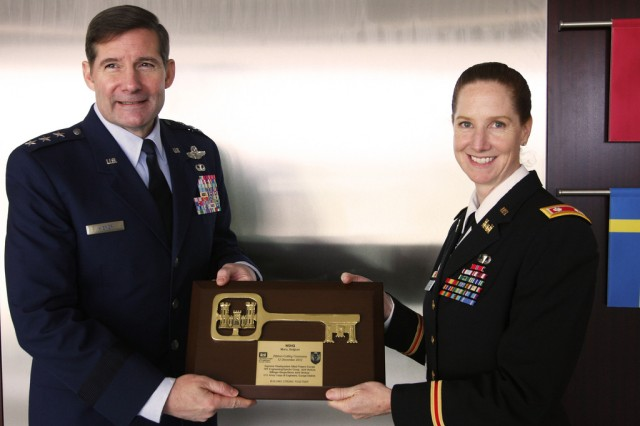 Lt. Col. Michelle Garcia, the U.S. Army Corps of Engineers Europe District deputy commander, presents a commemorative key plaque to Lt. Gen. Frank Kisner, NATO Special Operations Headquarters commander, during the facility ribbon-cutting ceremony Dec. 12 at SHAPE in Mons, Belgium. NATO special operations forces, comprised of 26 member nations and three non-NATO partners, have moved into a new state-of-the-art, 23,000-square-foot administrative headquarters building.