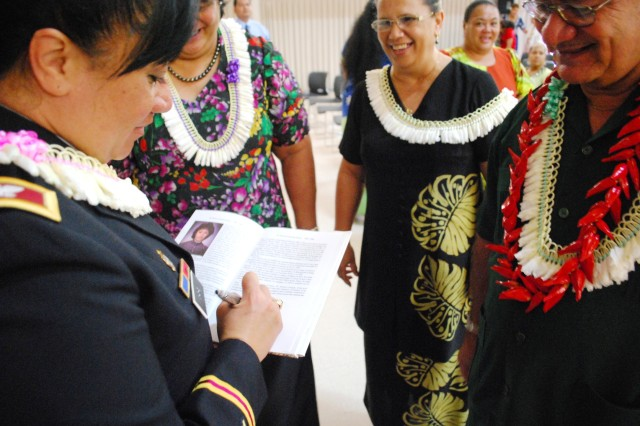 "Col. Leafaina Yahn, commander, 404th Army Field Support Brigade, signs her featured page in former Samoan Gov. Togiola Tulafono's copy of the book ""The 100 Women of American Samoa."" Yahn is a graduate of the U.S. Military Academy and the first for Samoa. (Photo by Greg Alderete, 404th AFSB Public Affairs)"