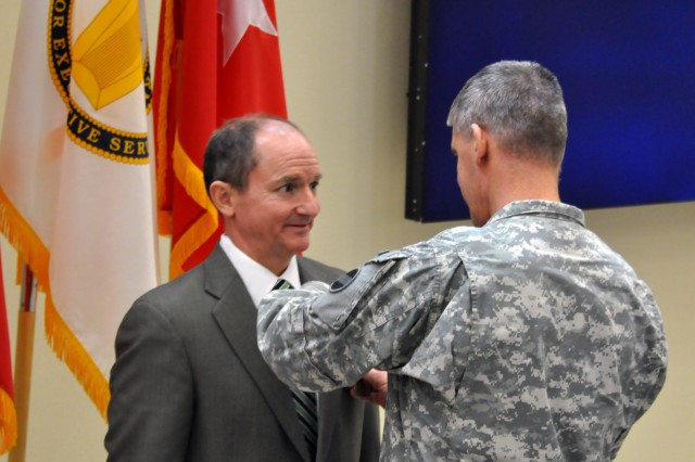 Gen. David M. Rodriguez, commanding general, U.S. Army Forces Command (FORSCOM), presents the Meritorious Civilian Service Medal to Mr. Richard M. Holcomb, a member of the Senior Executive Service, during a General Officer/Senior Executive Service member farewell ceremony, Jan. 25, 2013, in General George C. Marshall Hall, at Fort Bragg, N.C. Holcomb who had served as the command's deputy chief of staff, G8 (comptroller), is currently serving in that capacity at U.S. Army Special Operations Command at Fort Bragg.
