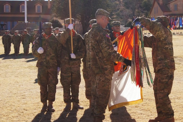 From left, Col. Patrick Dedham, brigade commander, 11th Signal Brigade, and Command Sgt. Maj. Earl Allen, commander sergeant major, 11th Signal Brigade uncase the brigade colors on Brown Parade Field, Jan. 17. The ceremony symbolizes the unit's official return home.