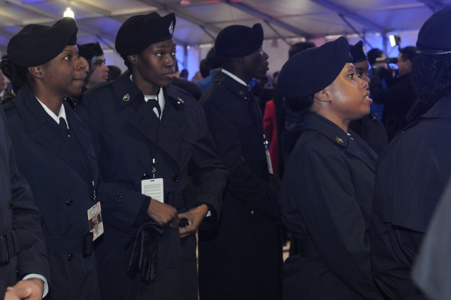 (Rear left) Chief Warrant Officer 2 Monique Perkins, a human resource officer at the 80th Training Command headquarters, and Staff Sgt. Wilnessial Kingdom, executive administrative assistant 80th Training Command, watch presidential inauguration activities on an oversized video monitor before marching in the 57th Inauguration Parade in Washington, D.C., Jan. 21, 2013.