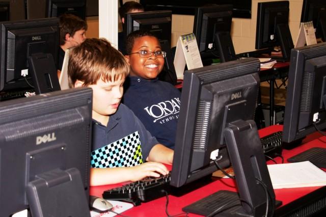 Adam Hyder (left) and Jaylen Gore, fifth-graders at Jordan Catholic School, Rock Island, Ill., enjoy themselves during computer class, Oct. 19, 2012.