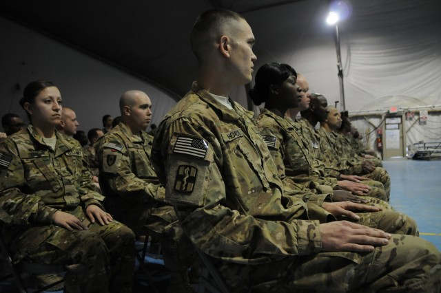 Twenty five noncommissioned officers from multiple Army Medicine units serving in Afghanistan sit poised to be inducted into the NCO Corps at Bagram Air Field, Jan. 25. (Army Photo by Maj. Charles Patterson, Task Force MED-A Public Affairs / Released)