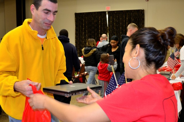 "FORT CAMPBELL, KY "" A Soldier with the 101st Airborne Division (Air Assault), receives a refurbished laptop from Operation Homelink at Fort Campbell's Family Resource Center, Jan. 26. Operation Homelink's goal is to support the members of the armed forces by bridging the gap of time and distance while separated during deployments. (U.S. Army photo by Sgt. Alan Graziano, 3rd BCT PAO, 101st Abn. Div.)"